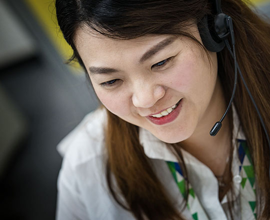 Asian woman dispatcher with headset, close-up