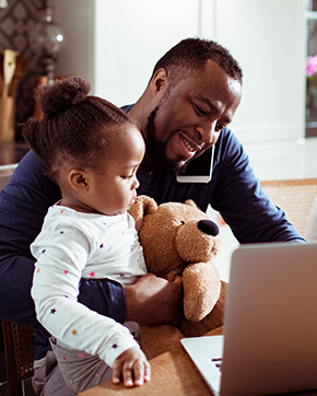 black dad working at home, holding toddler
