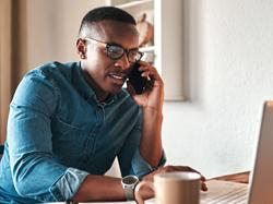 black man working from home, on phone at computer