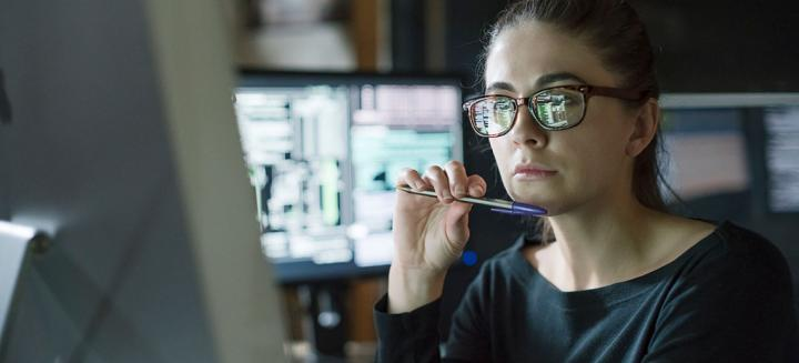 woman looking thoughtfully at computer monitor