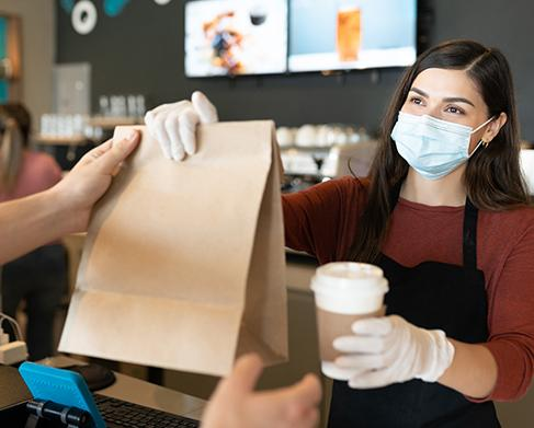 counter service, barista in mask hands bag and coffee to customer